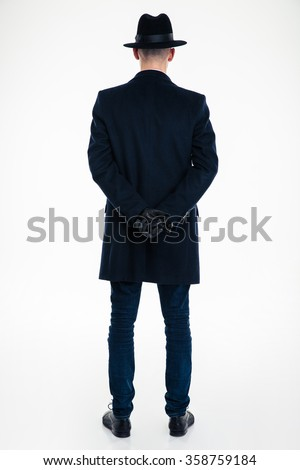 Back view of business man in black clothes and hat standing over white background - stock photo