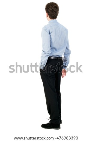 back view of Business man looks. Curly businessman in a light shirt looks into the distance.