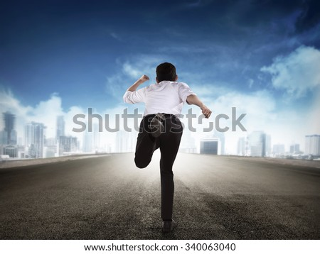 Back view of business man running to the city
