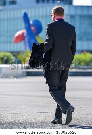 Back view of business traveler man walking with suitcase in the street - stock photo
