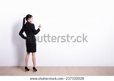 Back view of business woman writing something on white wall background, great for your design or text, asian - stock photo