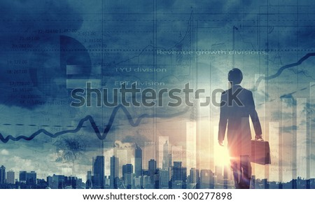 Back view of businessman and graphs at background - stock photo