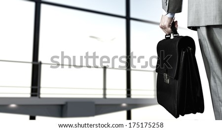 Back view of businessman at airport with suitcase in hand - stock photo