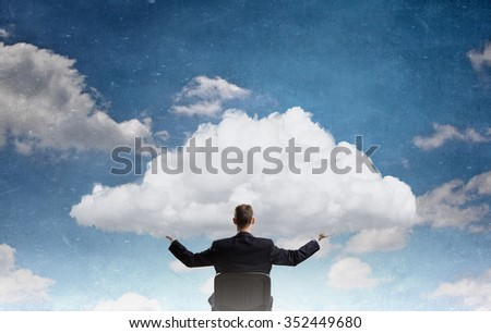 Back view of businessman in chair holding white cloud  - stock photo