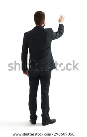 back view of businessman in formal wear raising up his hand like pushing screen. isolated on white background - stock photo