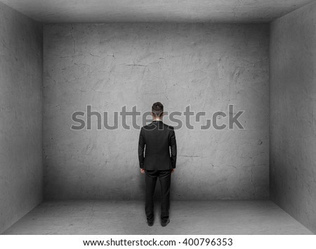 Back view of businessman inside empty concrete room