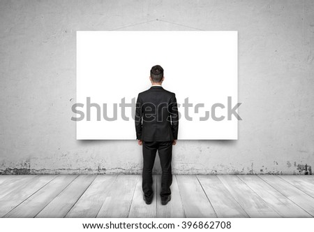 Back view of businessman looking at white empty canvas on concrete wall - stock photo
