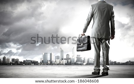 Back view of businessman on road with suitcase in hand - stock photo