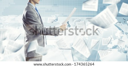 Back view of businessman reading documents in hand - stock photo