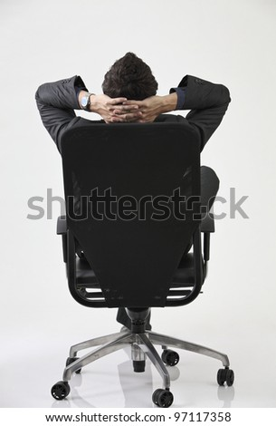 back view of Businessman relaxing in black chair - stock photo