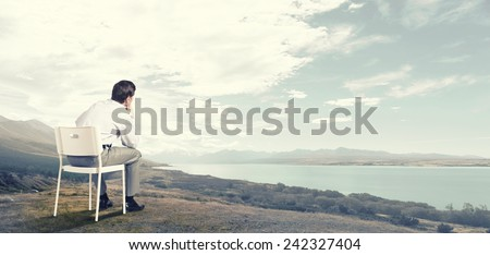 Back view of businessman sitting in chair and thinking - stock photo