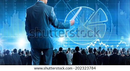 Back view of businessman speaker standing on podium with papers in hand - stock photo