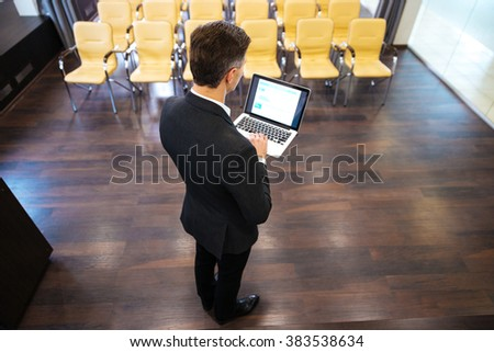 Back view of businessman standing and using laptop in conference hall - stock photo
