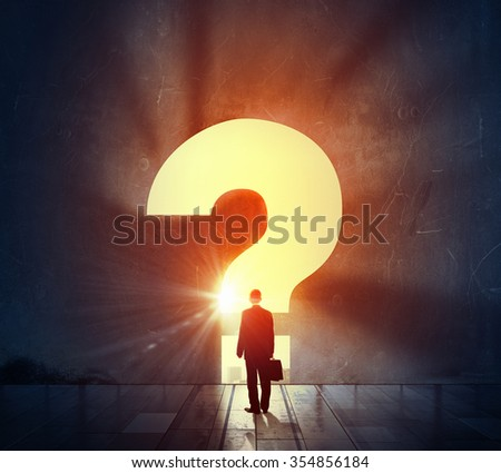 Back view of businessman standing in light of big question mark
