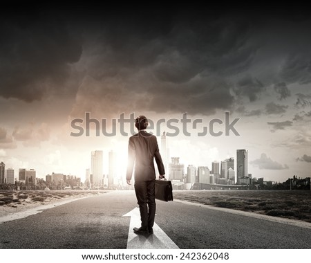 Back view of businessman standing on road and looking far away - stock photo