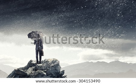 Back view of businessman with umbrella and suitcase standing on mountain top - stock photo