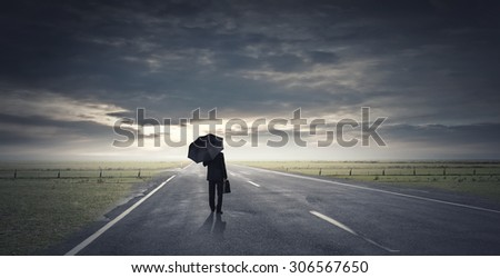 Back view of businessman with umbrella and suitcase walking on road - stock photo