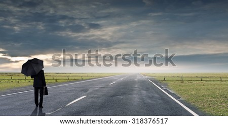 Back view of businessman with umbrella and suitcase walking on road