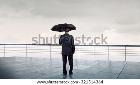 Back view of businessman with umbrella looking at city - stock photo
