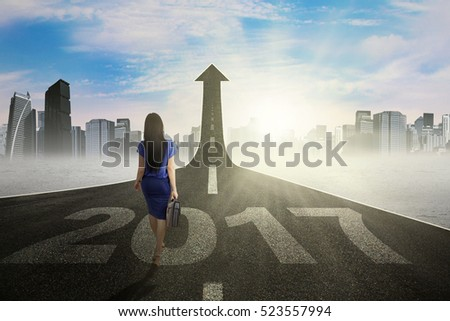 Back view of businesswoman carrying a briefcase and walking above numbers 2017 on the road while looking at road shaped arrow upward
