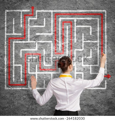 Back view of businesswoman drawing labyrinth on wall - stock photo