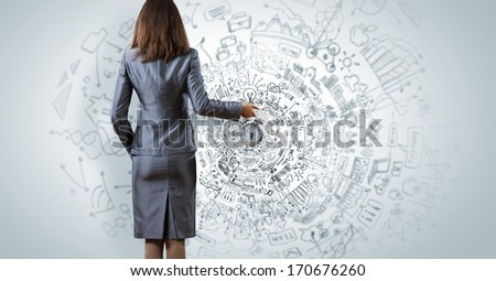 Back view of businesswoman holding alarm clock against sketch background - stock photo