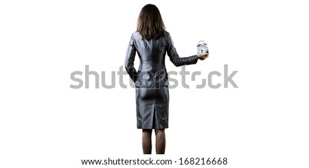 Back view of businesswoman holding alarm clock against white background - stock photo