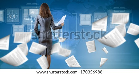 Back view of businesswoman holding papers in hands - stock photo