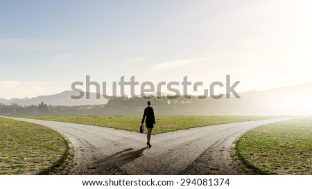 Back view of businesswoman standing on crossroads and making choice - stock photo