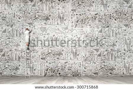 Back view of businesswoman standing on ladder and drawing sketch on wall - stock photo