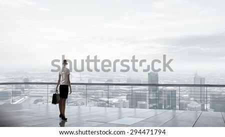 Back view of businesswoman standing on roof looking at city