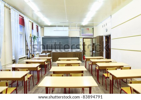 Back view of chairs in physics school class; blackboard with formula - stock photo