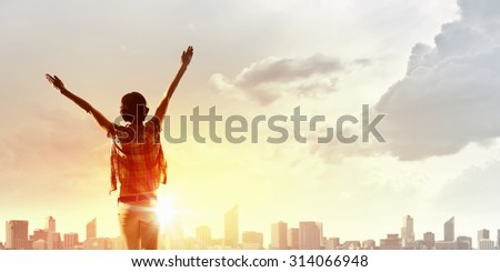 Back view of cheerful woman with hands up facing sunrise - stock photo