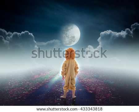 Back view of child costumed like a lion on pathway with a nightly sky and a large moon for halloween background. The moon taken with my own camera, no NASA images used. - stock photo