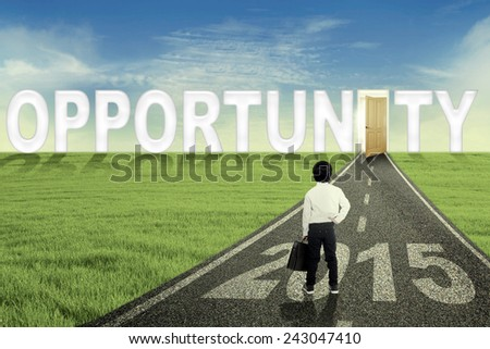 Back view of child holding briefcase and standing on the road with an opportunity door and number 2015 - stock photo