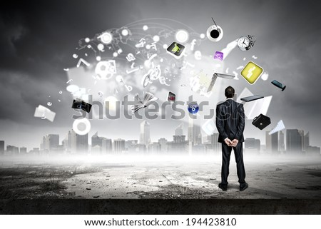 Back view of confident businessman looking at items flying in air