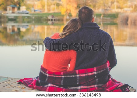 Back view of couple are sitting in warm clothes and blanket infront big lake - stock photo
