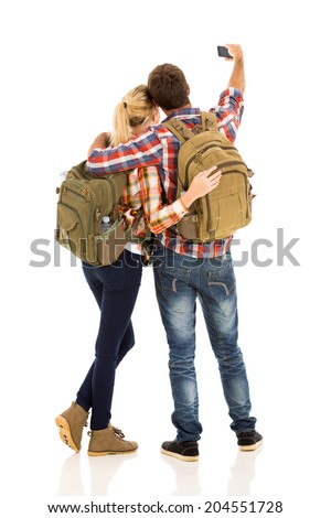 back view of couple taking selfie with their smart phone - stock photo