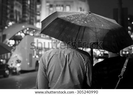 Back view of couple under the umbrella in the evening against the double-decker in London. Black-and-white image with selective focus - stock photo
