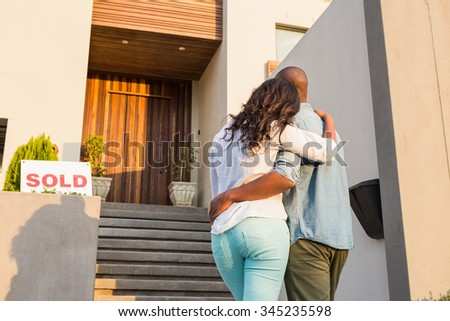 Back view of couple with arms above after buying house - stock photo