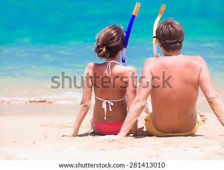 back view of couple with snorkel gear sitting on sand beach - stock photo