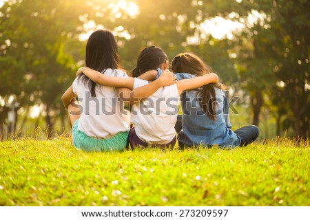 Back view of cute girls seated on green grass and relaxing