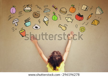 back view of cute kid imagine various foods with set of infographics over textured wall background - stock photo