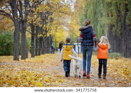 Back view of Cute kids with his dog labrador retrievers outdoor in autumn beautiful park - stock photo