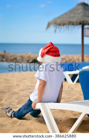 Back view of cute little boy in Santa hat on beach. Sunny exotic vacation outside on blue sky background - stock photo