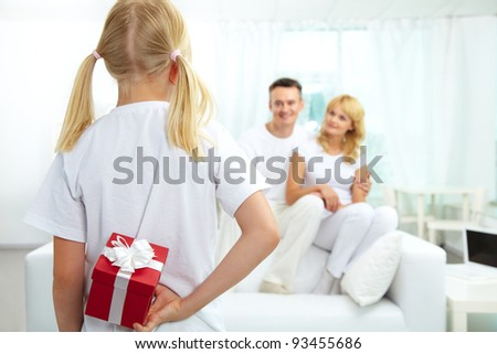 Back view of daughter hiding giftbox while looking at her parents - stock photo