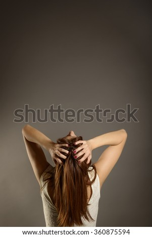 Back view of displeased, shocked, pissed off, angry, grumpy, pessimistic, woman with hands on head with bad headache, looking up, studio shot on gray with space for text. Negative human emotions