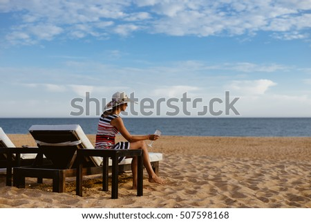 Back view of elegant lady relaxing on a chaise lounge, sandy beach outside background