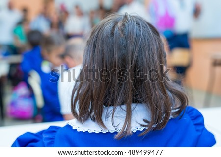 Back view of elementary schoolgirl in her classroom.