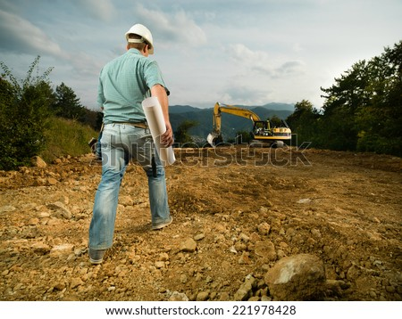 back view of engineer holding blueprint, walking on construction site towards excavator - stock photo